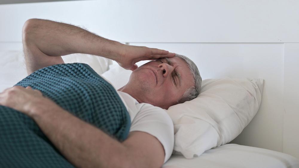 homem idoso de cama, com mão na cabeça, em sinal de dor. Sequelas da covid são variáveis