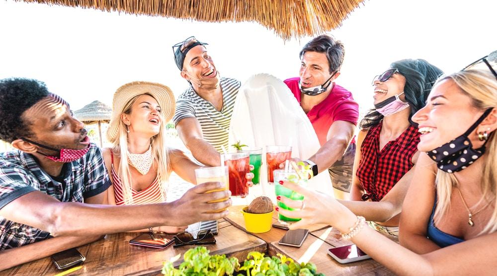 jovens com máscara pendurada no rosto, sentados em volta de mesa de bar brindando, como se fosse o fim da pandemia