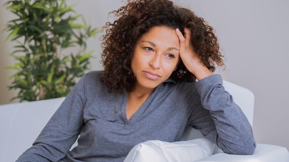 mulher triste sentada no sofá,com mão na cabeça. Setembro amarelo conscientiza sobre suicídio