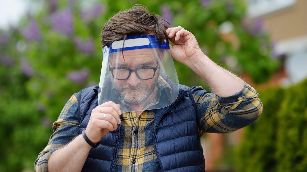 homem coloca protetor facial para evitar contágio pelo novo coronavírus