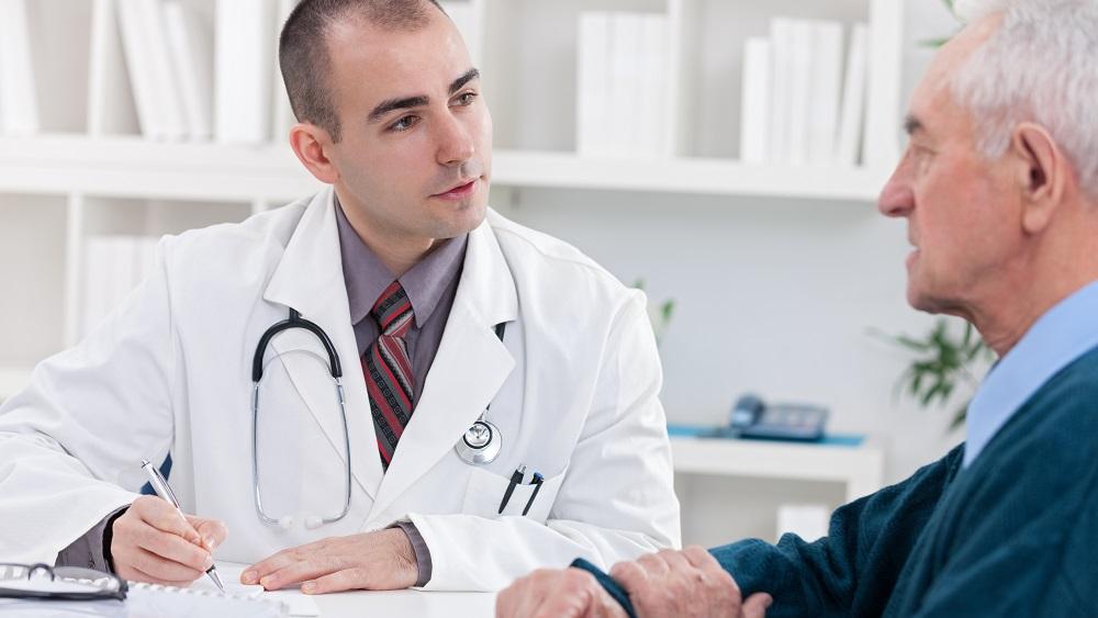 Médico conversa com paciente em consulta.
