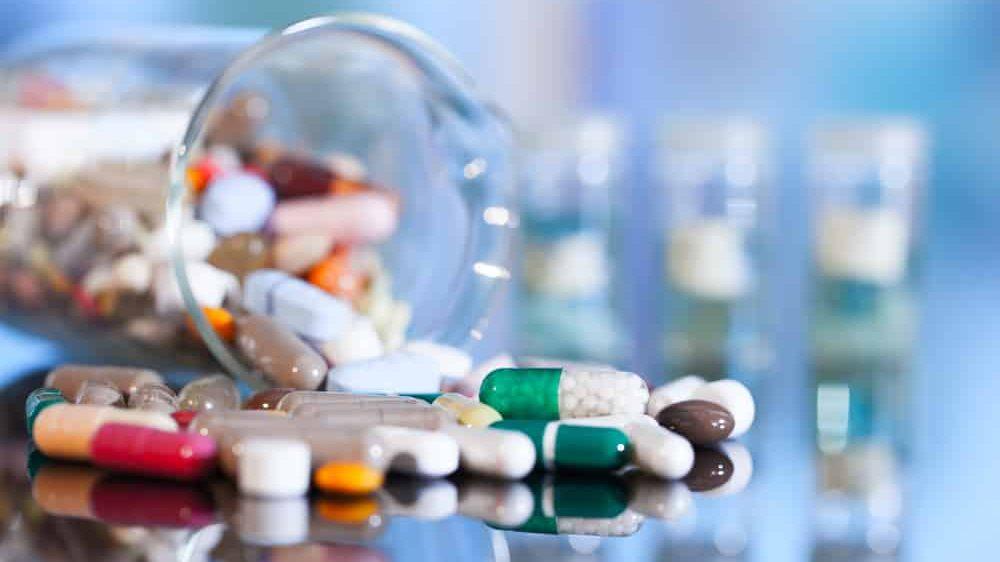 frasco derrubado com vários comprimidos de novos antibióticos caídos