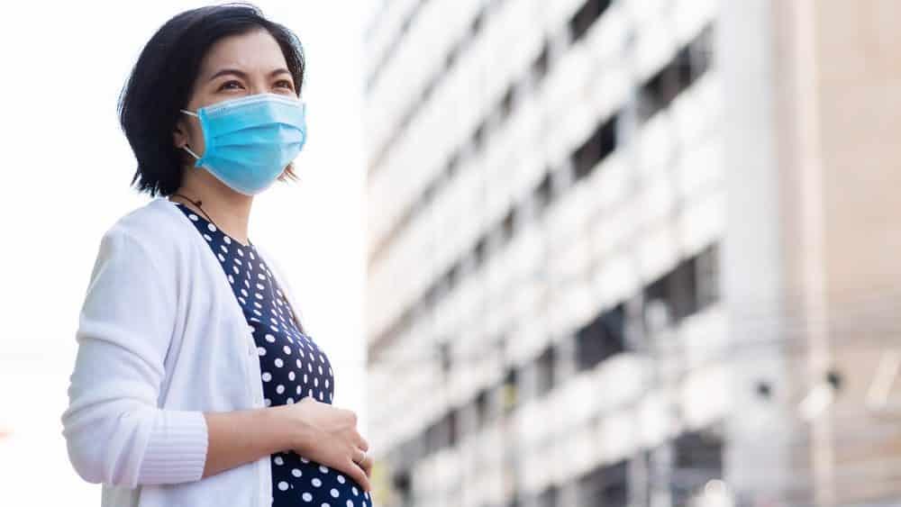 mulher grávida na rua, de máscara. gravidez e amamentação em tempos de covid-19 geram preocupação