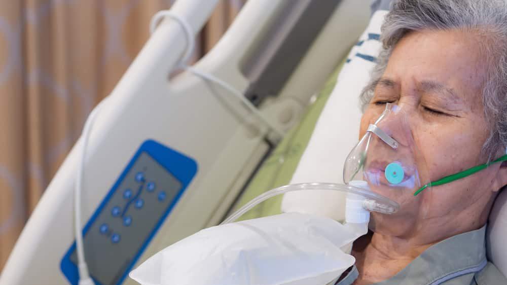 mulher idosa em leito hospitalar, com máscara de oxigênio para tratar edema pulmonar