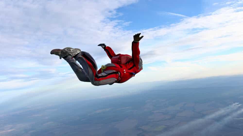 homem saltando de paraquedas. o paradigma do paraquedas explica por que é preciso ler estudos com atenção
