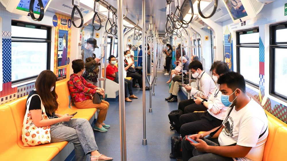 assintomáticos com máscara sentados em vagão de metrô