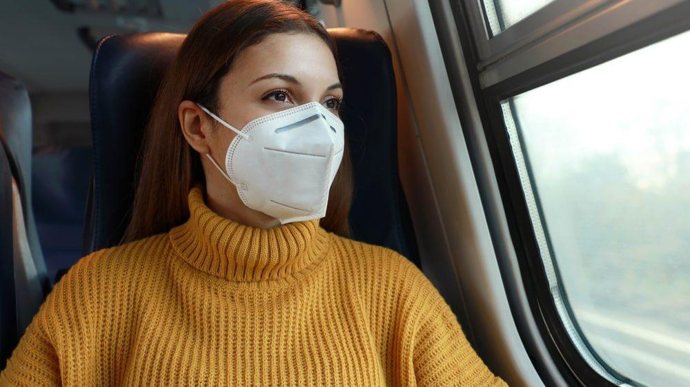 mulher de máscara viaja em transporte público. mutações do coronavírus preocupam