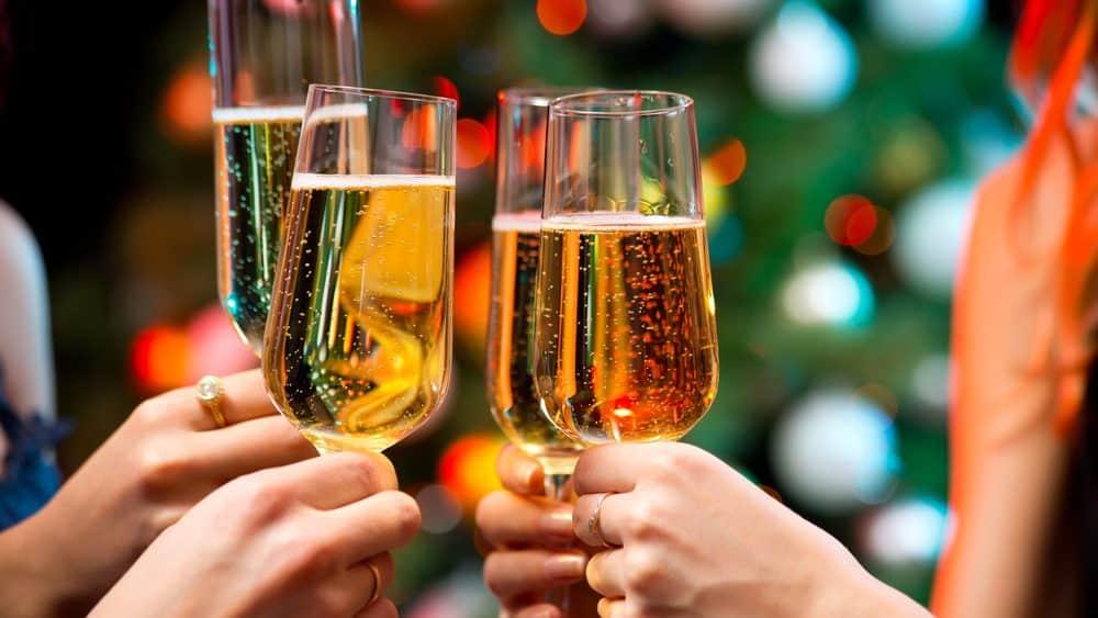 close em mãos segurando taça de champanhe, brindando o ano novo