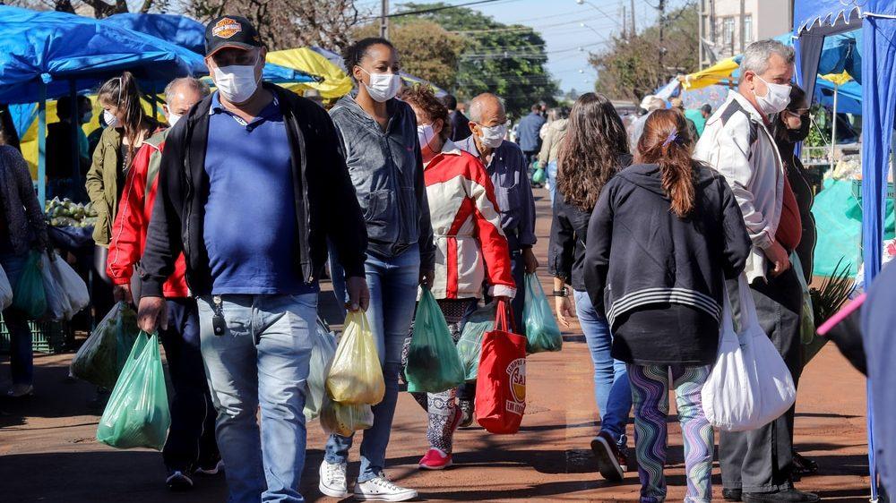 pessoas aglomeradas em feira no Brasil. Com mais variantes do coronavírus, aumentam os casos da doença