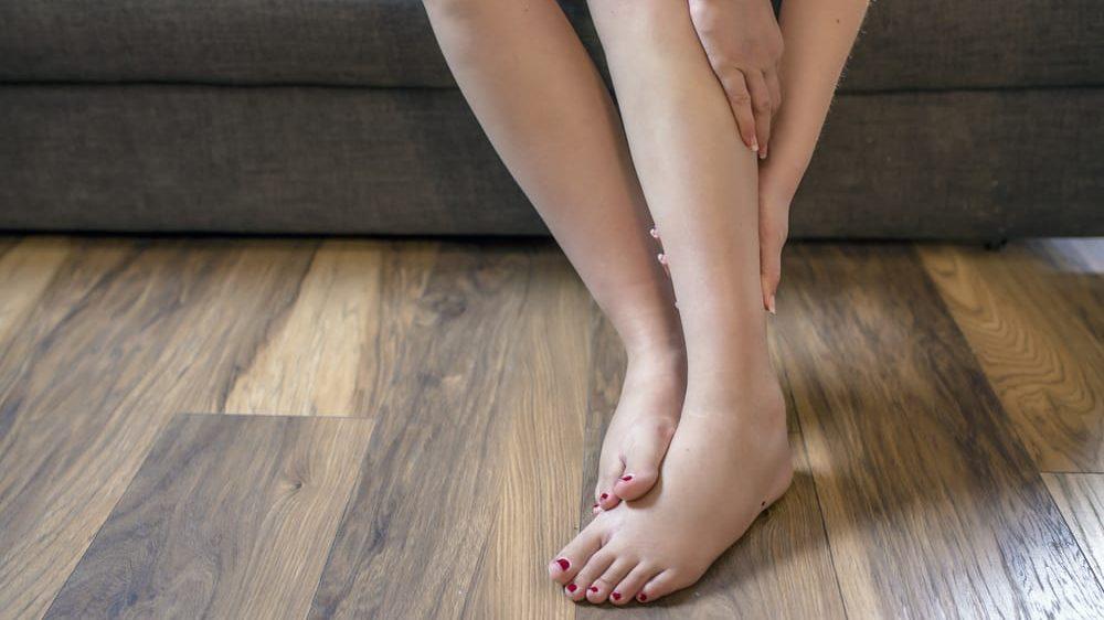 close em pernas inchadas de mulher sentada no sofá