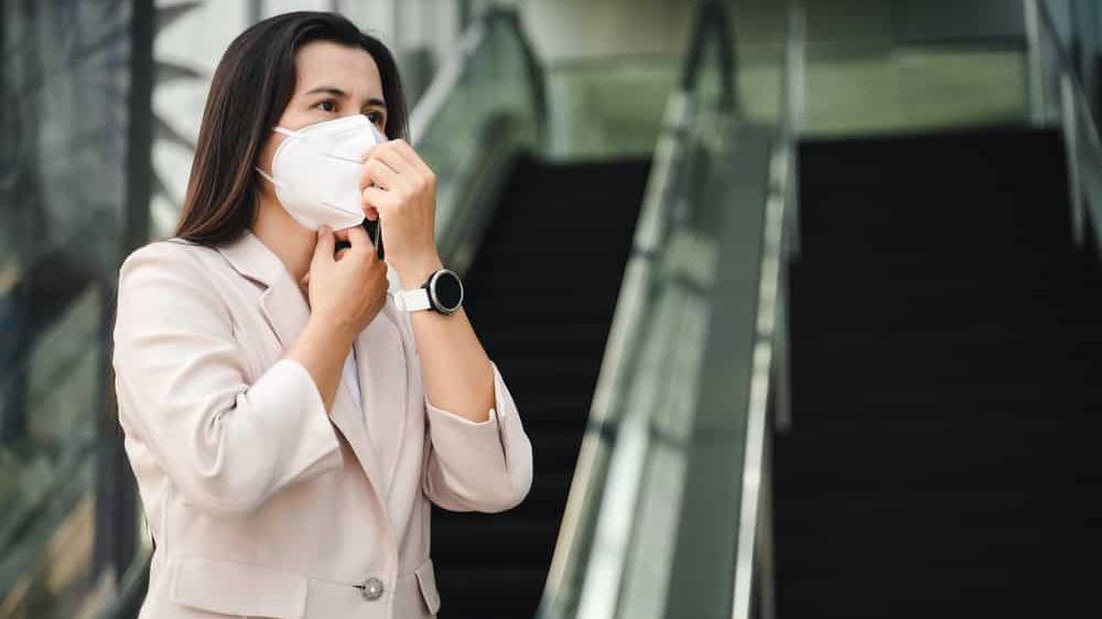 mulher vestida para o trabalho, em frente a escadas rolantes, usando máscara N95. Qual a melhor máscara para evitar a disseminação da covid-19?