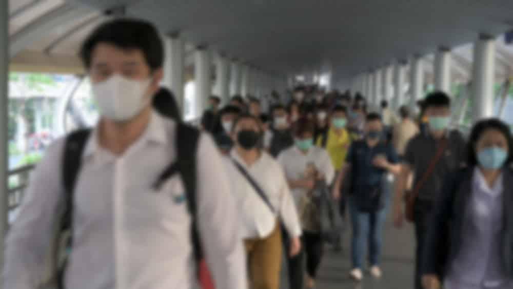 imagem desfocada de pessoas com máscara em lugar cheio durante a pandemia do coronavírus