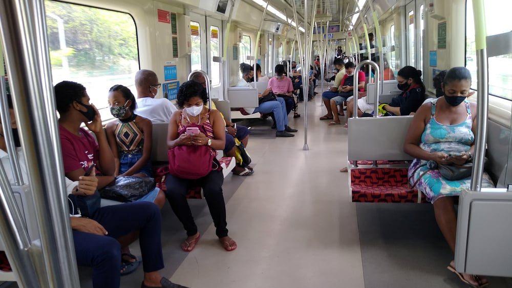 pessoas de máscara em vagão do metrô. não há mais grupos de risco para covid