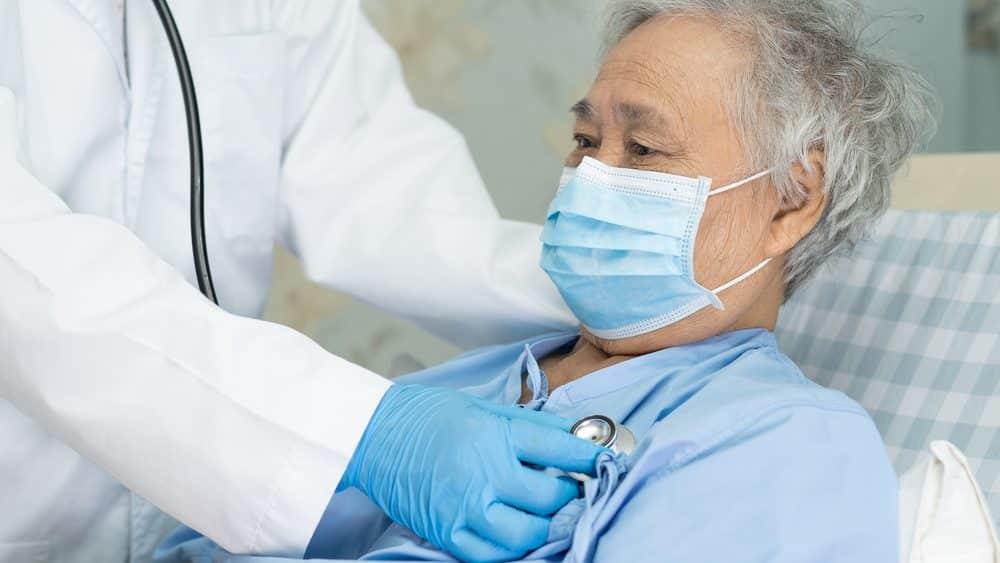 paciente com máscara em cama de hospital, sendo auscultado por médico. entenda a evolução da covid-19