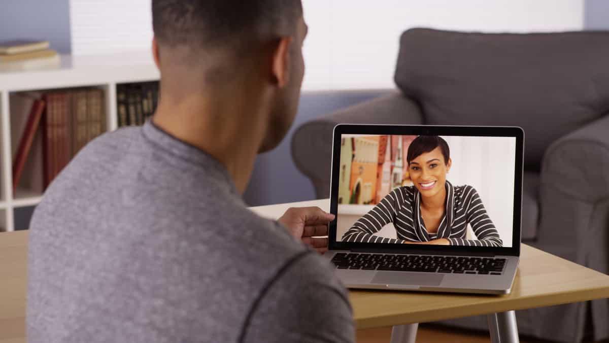 Homem faz vídeochamada com mulher pelo computador. Usar telas em excesso pode causar problemas de saúde.