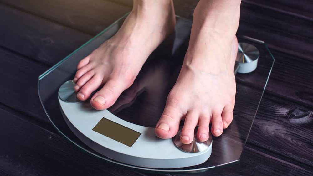 close em pés de pessoa se pesando em balança. Obesidade está associada a quadros mais graves de covid
