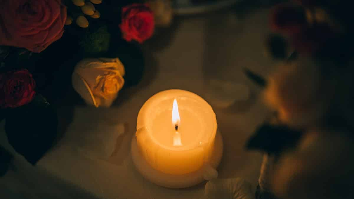 Vela acesa cercada de flores sobre uma mesa.
