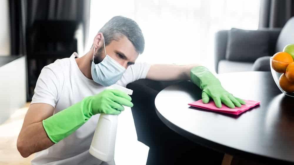 homem de máscara e luvas limpando superfícies para não contrair o novo coronavírus