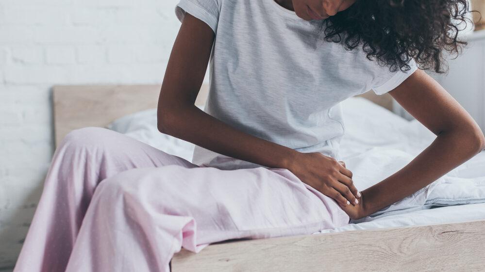 mulher com polimiosite sentada na cama com a mão no quadril, em sinal de dor