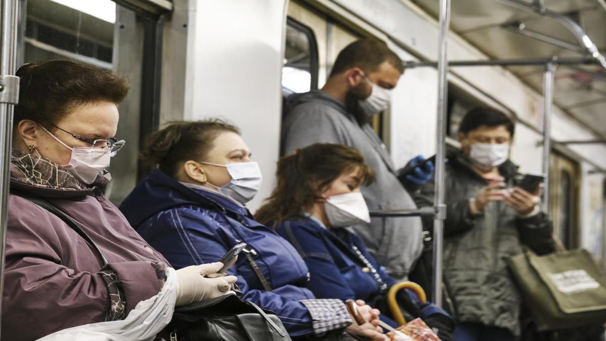 pessoas sentadas no metrô, com máscara, para se protegerem da variante delta do novo coronavírus