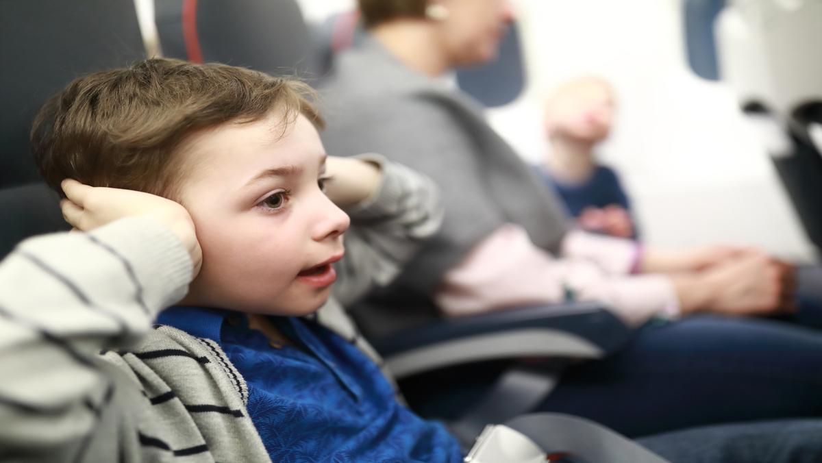 criança em avião com mãos nos ouvidos em sinal de dor por barotrauma da orelha média